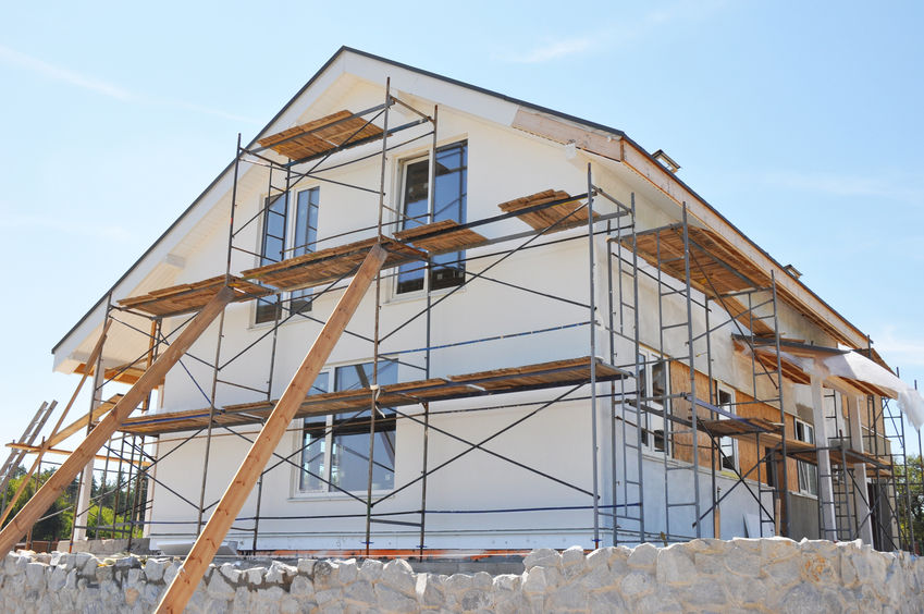 Painting facade house walls after renovation with stucco, plaste